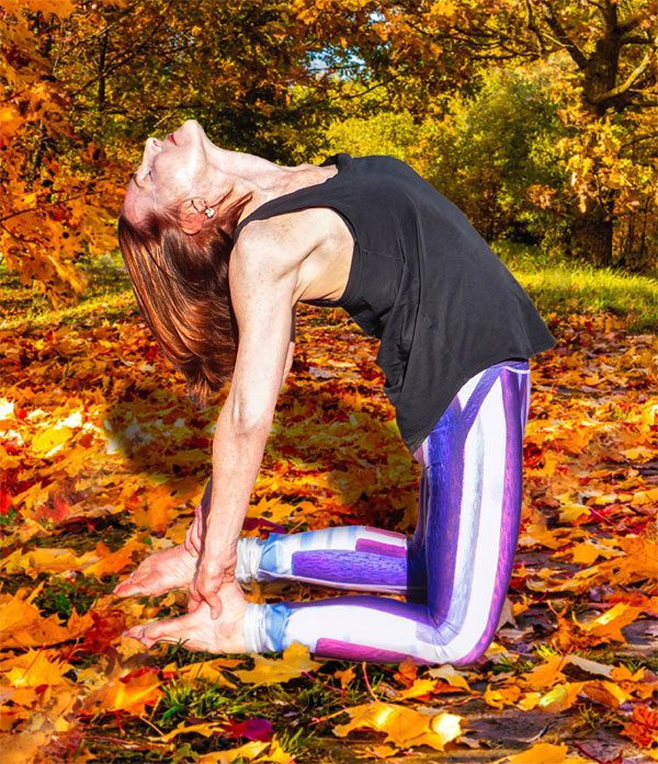 Ahna performing yoga in a scene of fall leaves