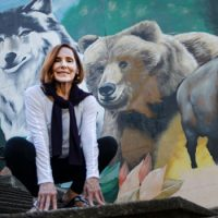 Ahna crouching in front of a wildlife mural with a worlf, a bear, and a bison